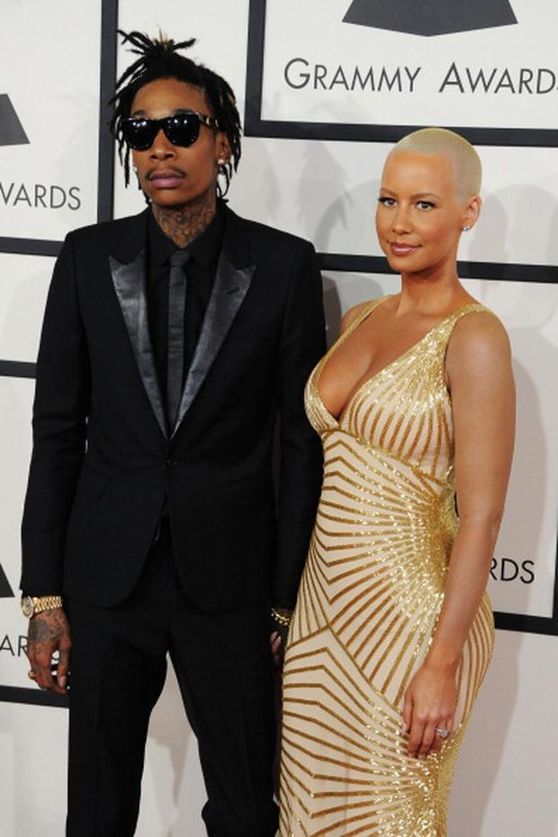 Recording artist Wiz Khalifa (L) featured wearing Converse in support of the GRAMMY Foundation's GRAMMY Camp and model Amber Rose attend the 56th GRAMMY Awards at Staples Center on January 26, 2014 in Los Angeles, California. (Photo by Steve Granitz/WireImage)