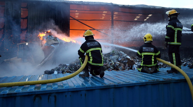 Members of the Dublin Fire Brigade spray water in to the bucket of a digger carring burning waste material from the fire at the Oxigen recycling plant in Ballymount. Pic Frank Mc Grath