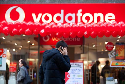 A pedestrian uses a mobile device as balloons sit beneath a sign outside a Vodafone store