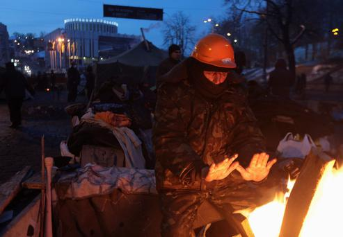 An anti-government protester warms himself by a fire in Independence Square in Kiev