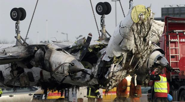 Emergency workers remove the wreckage of the Manx2 Fairchild turboprop plane from the runway at Cork Airport