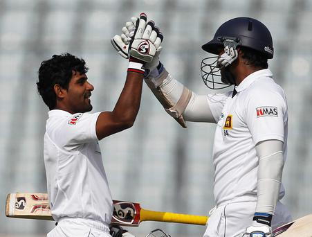 Sri Lanka's Kumar Sangakkara (R) congratulates teammate Kaushal Silva on scoring a century against Bangladesh during their second day of first test cricket match of the series in Dhaka January 28, 2014