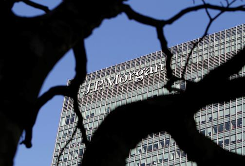 A sign on the Canary Wharf offices of JP Morgan is seen through the branches of a tree in London January 28, 2014. Police said they are investigating the