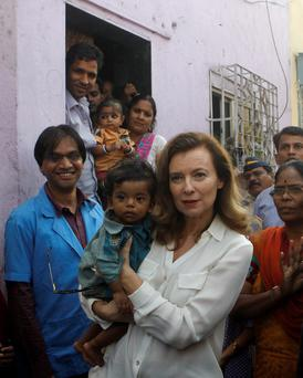 Valerie Trierweiler, former French first lady, holds a child as she visits a slum in Mumbai
