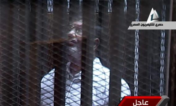 In this image taken from Egypt State TV, Egypt's toppled President Mohammed Morsi stands inside a glass-encased metal cage in a courtroom in Cairo, Egypt, Tuesday, Jan. 28. 2014
