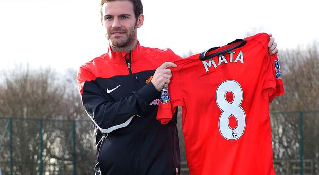 Manchester United's Juan Mata holds up his new No 8 jersey