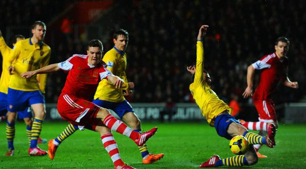 Sam Gallagher of Southampton takes a shot at goal that is blocked by Laurent Koscielny of Arsenal during the Barclays Premier League match