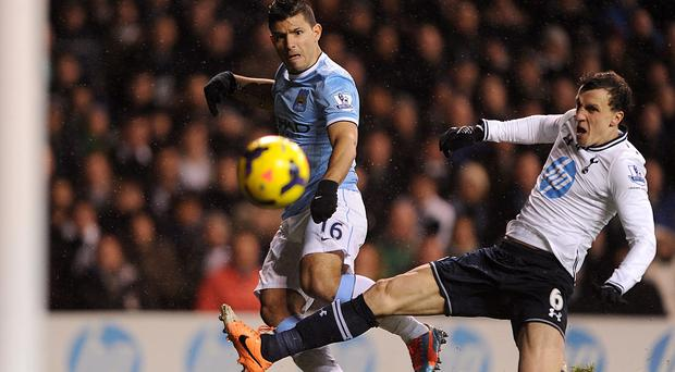 Tottenham Hotspur's Vlad Chiriches (right) slides in as Manchester City's Sergio Aguero has a shot on goal during the Premier League match at White Hart Lane