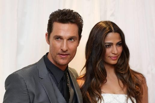 Matthew McConaughey (L) and his wife Camilla Alves pose for photographs as they arrive for the UK Premiere of