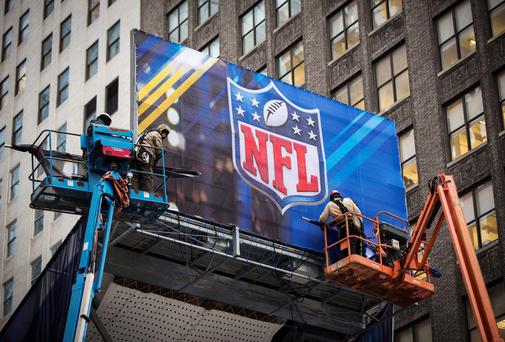 Workers hang signage on a booth on Broadway as preparations continue for Super Bowl XLVIII in New York. New Jersey's MetLife Stadium will host the first outdoor, cold-weather Super Bowl February 2. Reuters