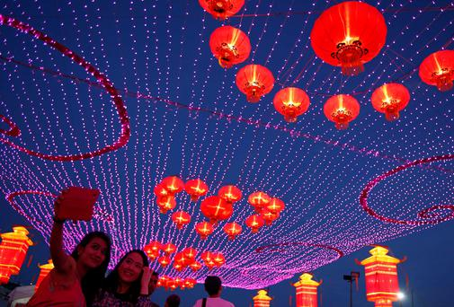 Revelers take photos of themselves during Chinese New Year celebrations ahead of the new year at Marina Bay in Singapore. Reuters