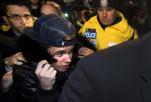 Justin Bieber is swarmed by media and police officers as he turns himself in to city police for an expected assault charge, in Toronto. A police official said the charge has to do with an alleged assault on a limo driver in December. AP