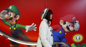 A shopper rides an escalator past Nintendo advertisements at an electronics retail store.