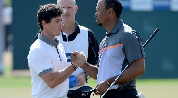 Rory McIlroy and Tiger Woods shake hands on the 9th green