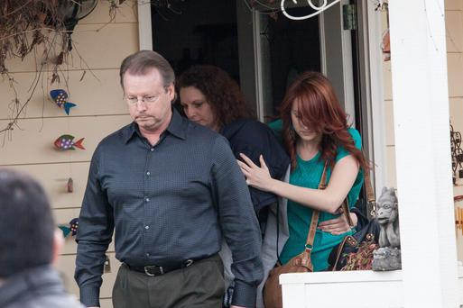 Amanda Knox ( with her head covered by clothing, leaves the home of her parents surrounded by others including her fathe on January 30, 2014 in Seattle, Washington.