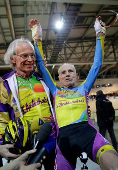 French cyclist Robert Marchand (R), aged 102, reacts with Gerard Mistler, President of the Ardechoise Cycling Club, after he covered 26.98 kms in one hour at the indoor Velodrome National in Montigny-les-Bretonneux, southwest of Paris