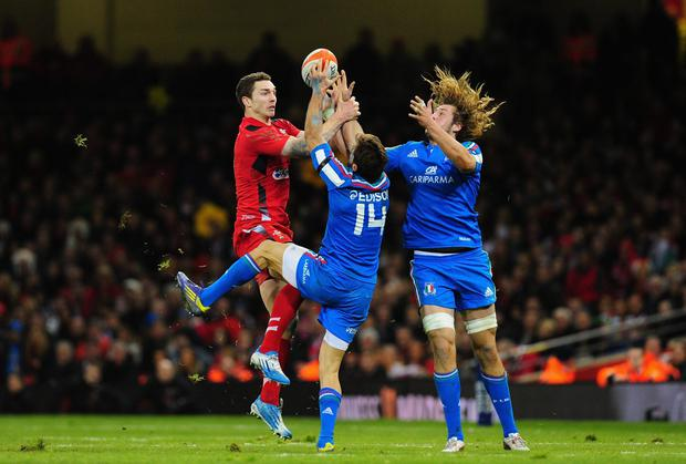 Wales player George North (l) contests a high ball with Angelo Esposito (c) and Joshua Furno (r) of Italy