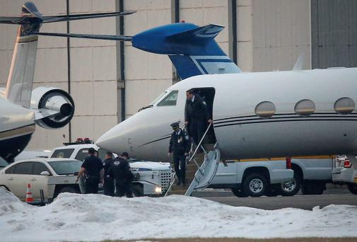 Law enforcement officers leave a plane belonging to Justin Bieber that was detained at Teterboro Airport in Teterboro, New Jersey