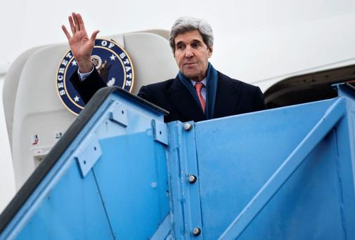US Secretary of State John Kerry waves while boarding his plane in Munich, southern Germany, yesterday