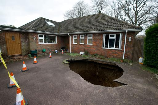 A view of the home of Phil and Liz Conran, in Main Road, Walter's Ash, High Wycombe, Buckinghamshire, after a 30ft-deep sinkhole opened up in the driveway yesterday and swallowed their car. PRESS ASSOCIATION Photo. Picture date: Monday February 3, 2014. See PA story ENVIRONMENT Sinkhole. Photo credit should read: Steve Parsons/PA Wire