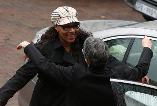 Zenani Mandela (L), daughter of former South African President Nelson Mandela gets a hug from Sahm Venter ahead of the reading of his father's will