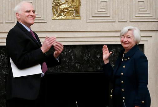Federal Reserve Board Governor Daniel Tarullo (L) applauds new Federal Reserve Board Chairwoman Janet Yellen after administering the oath of office tat the Federal Reserve Board in Washington