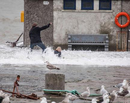 A man takes two young kids to Bullock harbour in south county Dublin during todays storm and high tides despite the recent warnings from the coast guards & emergency services. The young children were knocked over by a wave and were extremely lucky not to have been washed into the harbour.