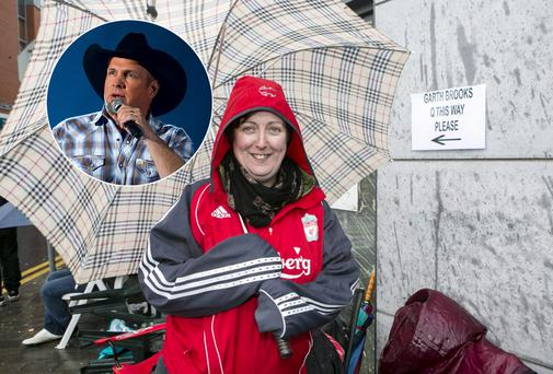 Sandra O'Shea queuing in the rain outside Ticketmaster in Limerick for tickets to see Garth Brooks, inset,