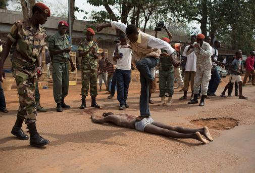 A man jumps on the corpse of a man, who was killed as he was accused of joining the ousted Seleka fighters, in the capital Bangui
