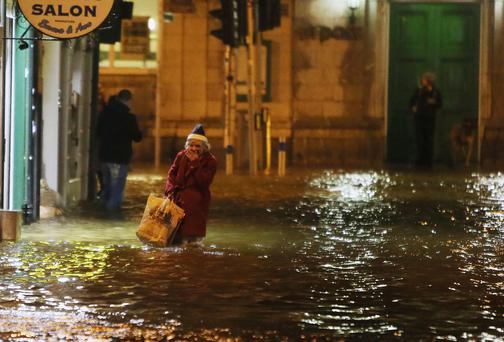 A woman walks through flood water in Cork city earlier this year