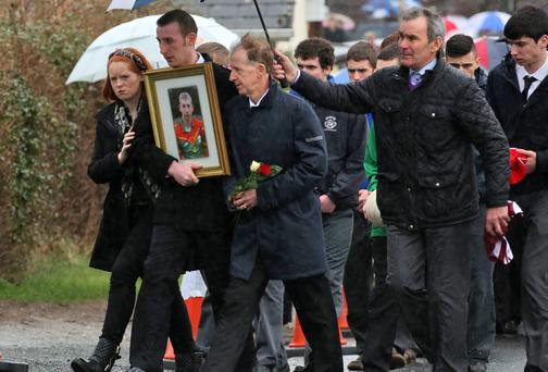 Father Joe Byrne, far right, father of Jonny Byrne, left, with his son Patrick who is holding a picture of his brother as they walk behind Jonny's remains after the funeral Mass at St Lazarian's Church, Leighlinbridge, Co Carlow. FRANK McGRATH