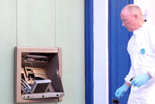 A forensic examiner surveys the damaged ATM in Enniscorthy, Co Wexford. Photo: Mary Browne