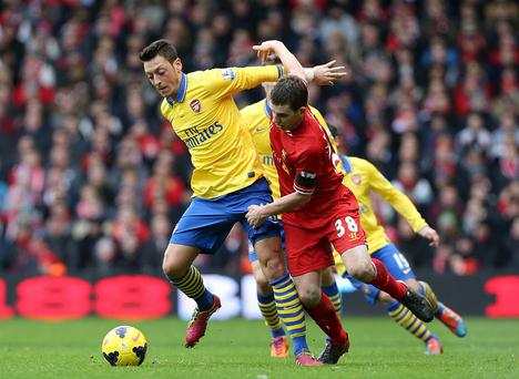Arsenal's Mesut Ozil (left) and Liverpool's Jon Flanagan battle for the ball during the Barclays Premier League match at Anfield, Liverpool. PRESS ASSOCIATION Photo. Picture date: Saturday February 8, 2014. See PA story SOCCER Liverpool. Photo credit should read: Peter Byrne/PA Wire. RESTRICTIONS: Editorial use only. Maximum 45 images during a match. No video emulation or promotion as 'live'. No use in games, competitions, merchandise, betting or single club/player services. No use with unofficial audio, video, data, fixtures or club/league logos.