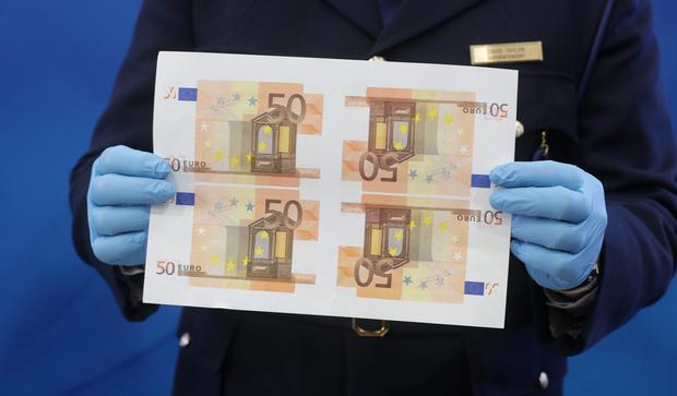 A Garda holds sheets of counterfeit €50 notes seized. Picture: Damien Eagers