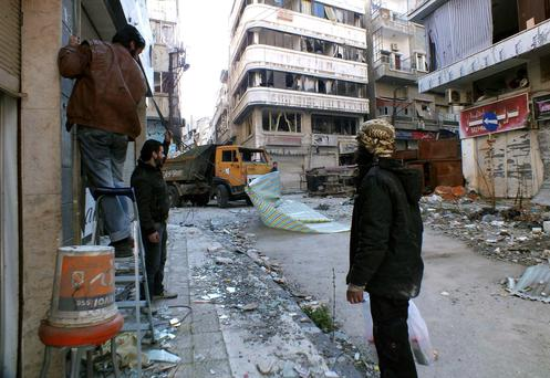 Activists hang a cloth screen to block the view of snipers prior to the arrival of the United Nations members to the besieged neighbourhoods of Homs to supply humanitarian aid