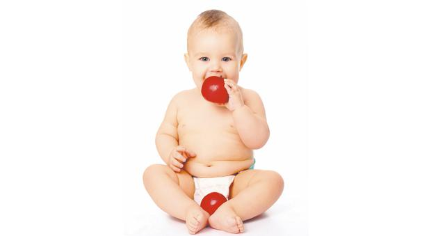 Happy baby eating fruit. Photo by Thinkstock