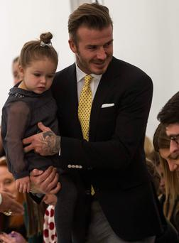 David Beckham holds his daughter Harper before the Victoria Beckham Fall 2014 collection during New York Fashion Week February 9, 2014. REUTERS/Eric Thayer