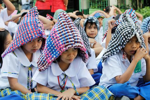 Elementary school pupils use doormats as improvised protective headgears as they stay in a safe area during an earthquake drill in Paranaque city, metro Manila February 10, 2014.