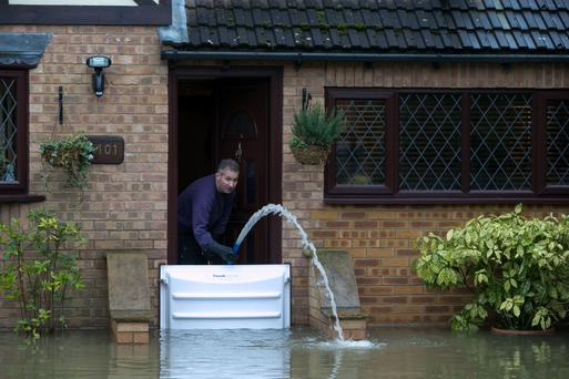 A resident pumps out water from his house in Wraysbury, Berkshire