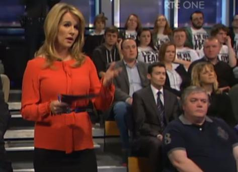 Members of the audience can be seen in the background wearing the t-shirts.