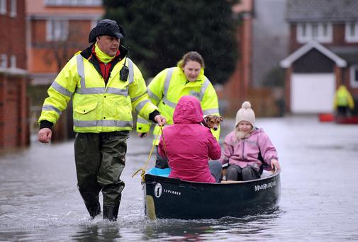 Volunteers help residents brave the flood water in Purley on Thames in southern England