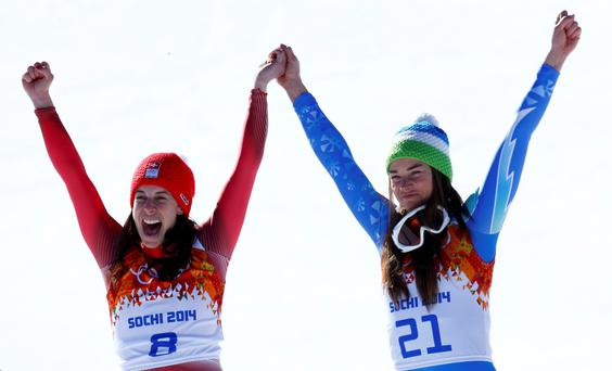 Joint winners Dominique Gisin of Switzerland (L) and Tina Maze of Slovenia celebrate on podium after the women's alpine skiing downhill event during a flower ceremony at the 2014 Sochi Winter Olympics.