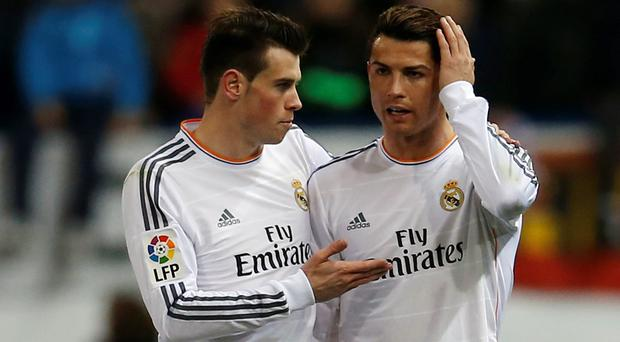 Real Madrid's Cristiano Ronaldo (R) listens to his team mate Gareth Bale after being hit with a lighter during their Spanish King's Cup semi-final second leg soccer match against Atletico Madrid.