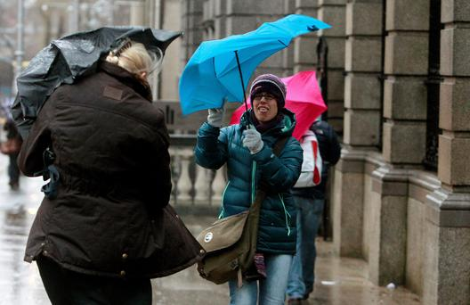 Pedestrians in Dublin's city centre struggle with their umbrellas as storms sweep across the country.