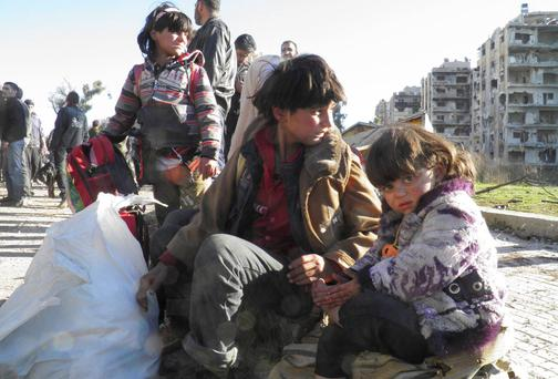 Children sit with their belongings as they wait to be evacuated from a besieged area of Homs