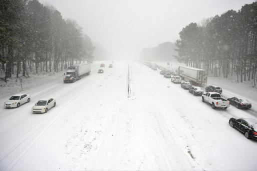 Traffic moves slowly along Wade Avenue on February 12, 2014 in Raleigh, North Carolina. Motorists were encouraged to stay off roads after Gov. Pat McCrory declared a state of emergency yesterday ahead of the winter storm.