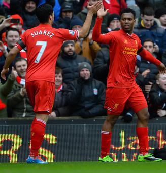 Daniel Sturridge of Liverpool celebrates scoring the fourth goal with team-mate Luis Suarez during the Barclays Premier League match between Liverpool and Arsenal at Anfield.