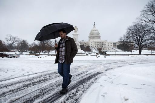 A man walks through the slush and shields himself from freezing rain on Capitol Hill in Washington, today, as winter weather shuts down Washington. Photo: AP Photo/J. Scott Applewhite