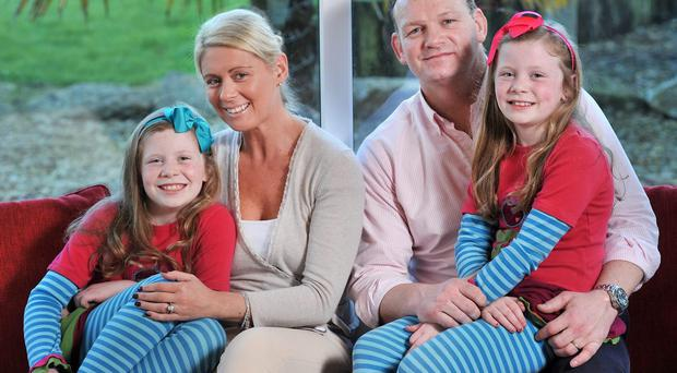 Former Munster and Ireland international David Corkery pictured in his Glanmire home with wife Eimear and twin daughters (8) Ann (left) and Ava