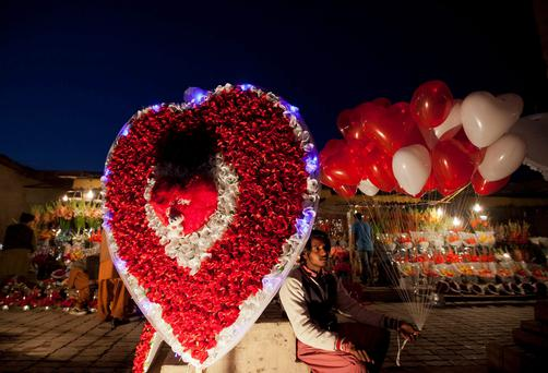 A man sits on a roadside next to a paper-flower decoration as he holds heart-shaped balloons, waiting for costumers on the ahead of Valentine's Day in Islamabad in Pakistan. Photo: Reuters/Mian Khursheed